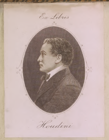"Houdini's bookplace incorporates a profile view of himself, facing left, in an oval frame. He has short curly hair and is wearing a suit and white shirt with a high collar, and a bow tie. Above the frame in cursive are the words ""Ex Libris"" and below is the name ""Houdini""."