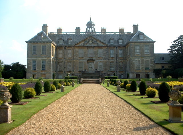 Image of a beautiful Belton House in Lincolnshire, an avenue with topiary bushes either side, leading up to a grand four-story building with wings to the right and left, and a central entrance up a shallow set of steps.