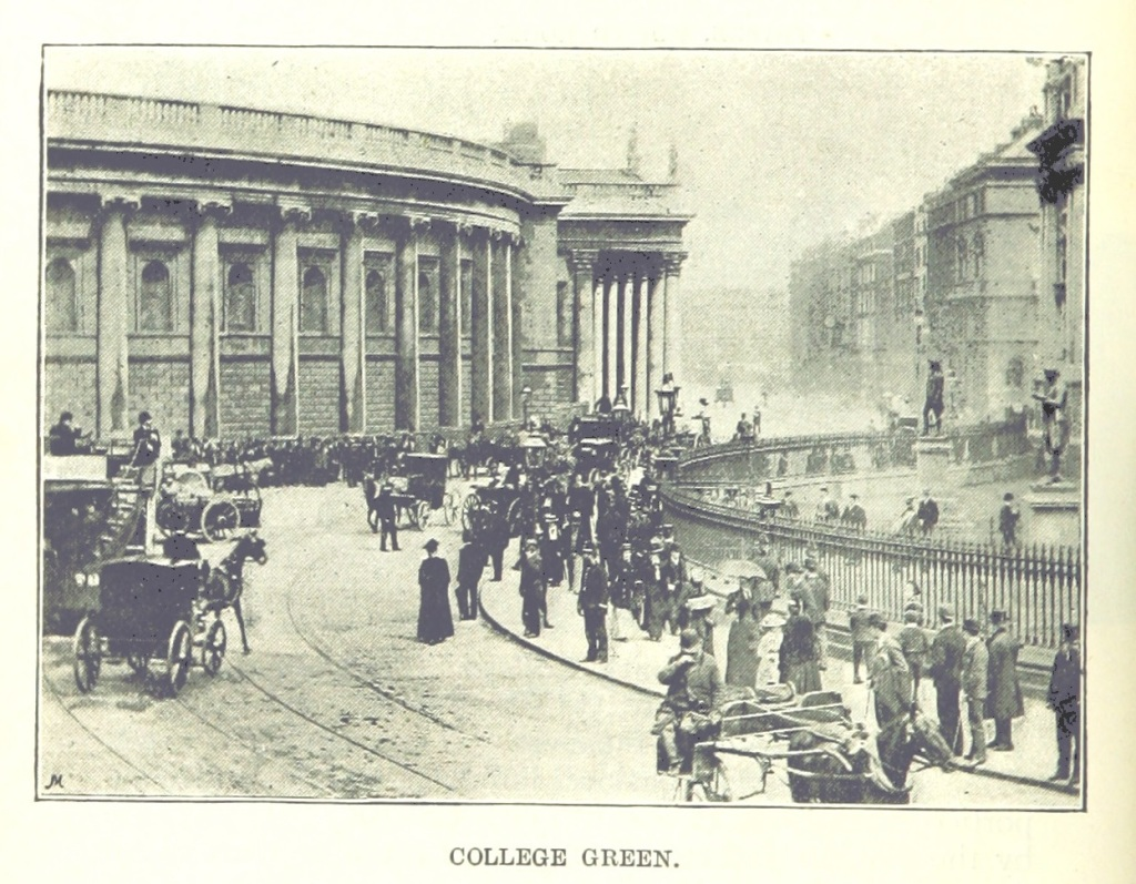 View of a Dublin street, containing a large number of pedestrians and several carriages. The gates of Trinity College are visible to the right and the Bank of Ireland Building is at the front and centre of the image.