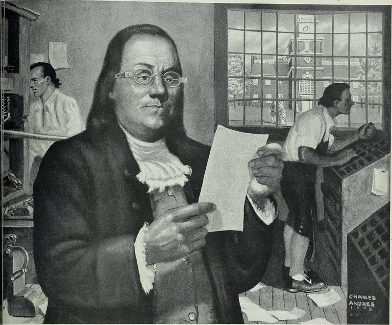 A reproduction of a famous portrait of Benjamin Franklin, represented at a printing office. Two men are working in the background: one is setting type and the other is handling a press. Franklin stands in the foreground, dressed in a coat and ruffled neckerchief and wearing glasses. He is holding up a piece of paper and his expression is confused, which is probably an unintentional result of the picture being reproduced for a magazine.