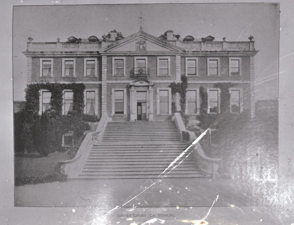 Image of a large old-fashioned house, with a large external staircase leading up to the front door. Two rows of windows are found across the whole front of the house. Parts of the front of the house are covered in ivy.