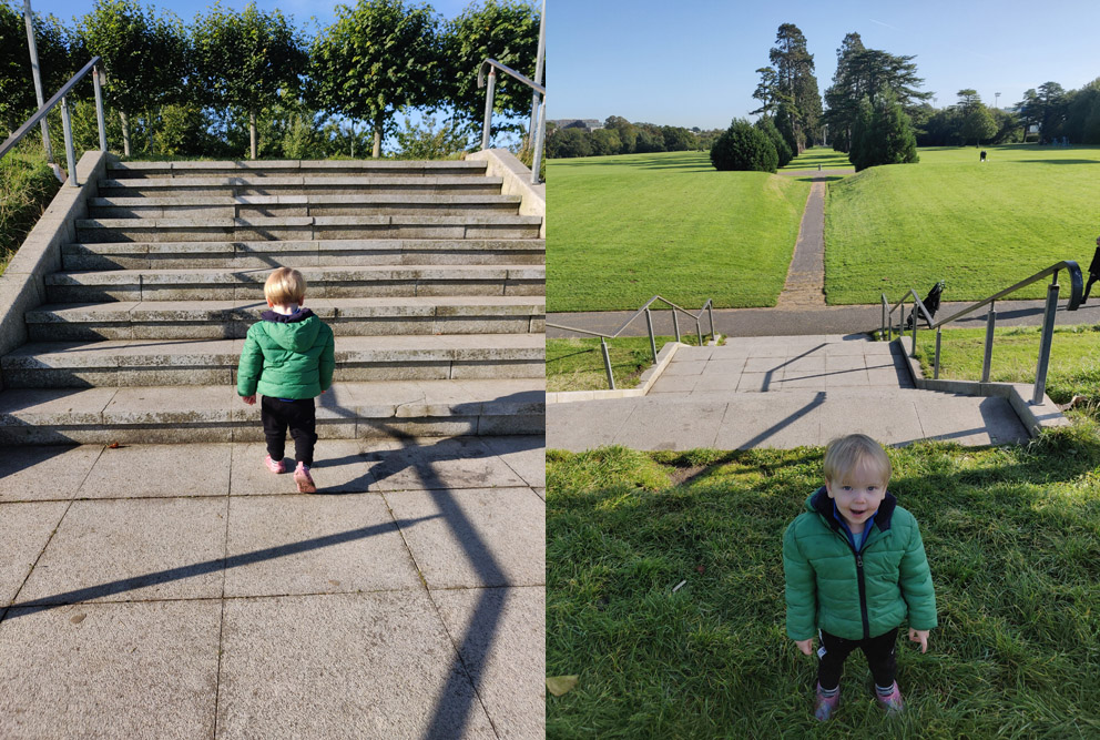 Two images are placed side by side. In the first image, which was taken in 2019, a small child in a green coat climbs a set of modern, concrete steps, while his back is turned to the camera. A stand of trees are visible at the top of the steps. In the second image, the same boy is standing facing the camera and smiling, at the top of the steps. From this viewpoint, it is possible to see down the steps and across an expanse of green grass. An avenue of trees appears down the centre of the grassy field.
