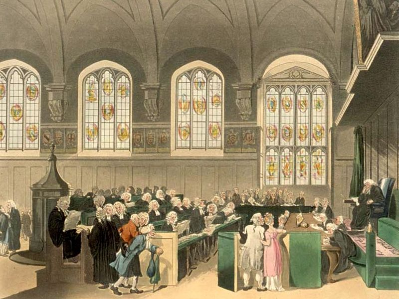 Engraved illustration of the court of Chancery at Lincoln's Inn, sometime around the year 1800. The room has a high, vaulted ceiling, with a row of tall, stained-glass windows along the back wall. Rows of lawyers are seated, wearing black gowns and white wigs; facing them is a seated judge on a raised stand, leaning on one elbow. A number of clerks are sitting in front of the judge at ground level, taking down notes. One lawyer is standing, addressing the judge, while in the foreground a few more are talking. In the foreground, a stooped old man in a blue coat is walking in, while a man and a woman are standing with linked arms looking anxiously at the judge: he is wearing a powdered wig, a white coat and breeches, while she wears a white petticoat with a pink gown over it. All the faces are drawn in a slightly comical style, a bit like caricatures.